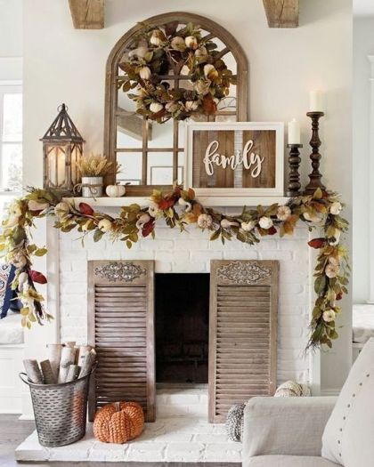 A-rustic-fall-mantel-with-dried-fall-leaves-and-pumpkins-candles-in-wooden-candle-holders-wheat-arrangements-and-a-rustic-sign-1