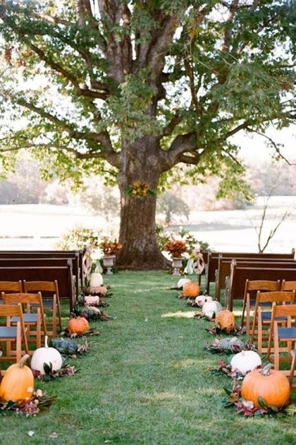 A-rustic-fall-wedding-ceremony-space-done-with-pumpkins-and-foliage-plus-fall-blooms-in-vintage-urns