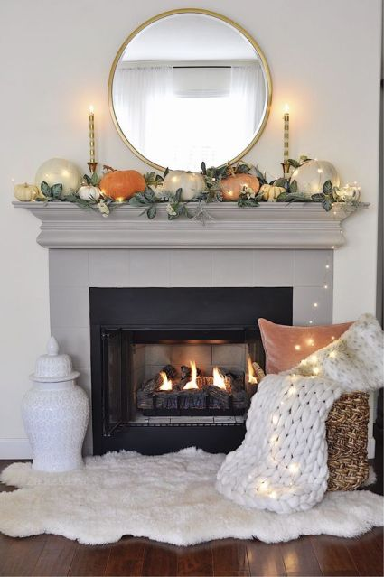 A-simple-contemporary-fall-mantel-done-with-greenery-and-pumpkins-of-muted-colors-plus-lights-all-over-it-1