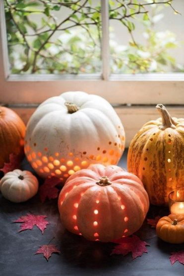 Perforated-pumpkin-in-various-natural-colors-and-with-candles-inside-are-very-chic-and-very-cozy-for-fall-decor