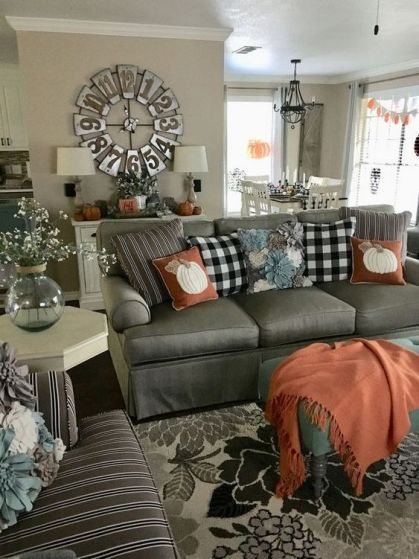 Rust-colored-textiles-and-plaid-pillows-make-this-farmhouse-living-room-very-fall-like