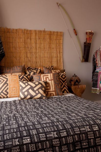04-this-calm-bedroom-boasts-of-a-cool-headboard-and-warm-colored-traditional-texiles-that-remind-of-africa