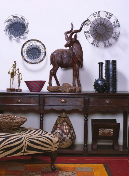 15-carved-console-table-with-a-zebra-printed-ottoman-and-african-artworks