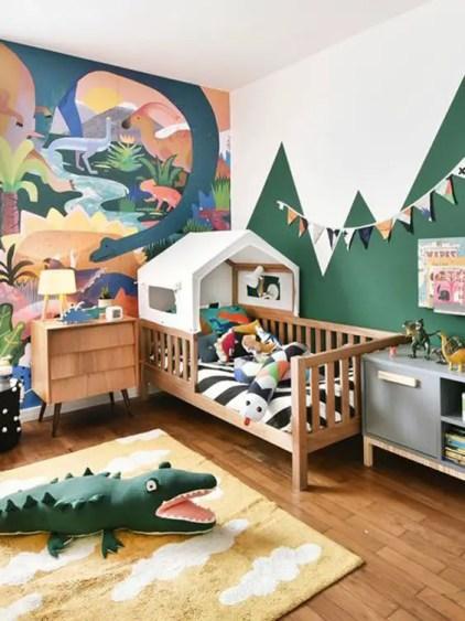Ein-helles-und-spaßiges-Dschungel-Themen-Kinderzimmer-mit-einem-mutigen-Kunstwerk-ein-Haus-Bett-und-buntes-Dschungel-inspiriertes-Spielzeug