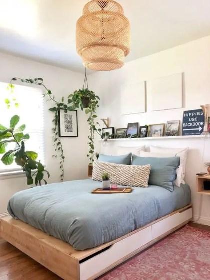Ein-zeitgenössisches-kleines-schlafzimmer-mit-einem-aufbewahrungsbett-ein-vorsprung-mit-einer-galerie-wand-einer-korblampe-und-eingemachtem-grun