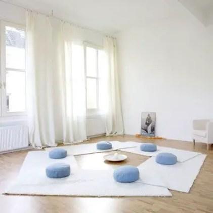 Ein-Heim-Meditationsraum-mit-weißen-Teppichen-und-blauen-Kissen-und-viel-Licht-und-Luft