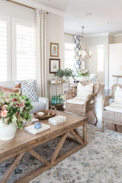 A-modern-country-living-room-in-neutrals-with-a-creamy-sofa-woven-chairs-a-low-coffee-table-printed-textiles-and-potted-plants