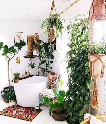 A-modern-meets-boho-bathroom-with-plants-in-hanging-pots-a-soak-tub-wooden-shelves-and-a-bold-boho-rug