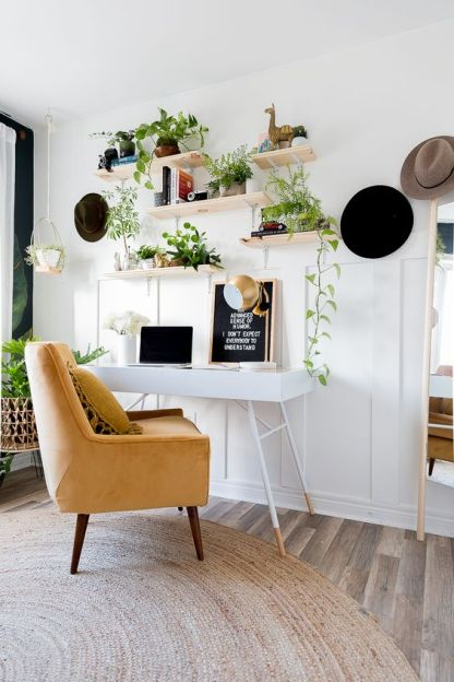 A-neutral-boho-home-office-with-a-tiny-desk-a-yellow-chair-and-open-shelves-with-climbing-plants-in-pots
