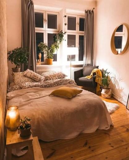 Ein-kleines-Boho-Schlafzimmer-mit-einem-großen-Bett-Topfgrün-gedämpfte-Farben-Textilien-und-einem-Spiegel-an-der-Wand