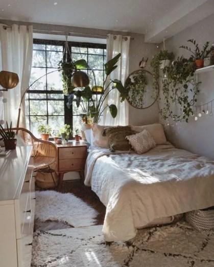 Ein-kleines-boho-schlafzimmer-mit-kaskadierendem-grün-in-töpfen-holzmöbeln-und-messinglampen