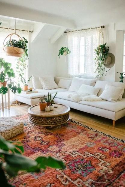 Ein-Boho-Wohnzimmer-mit-einem-neutralen-Schnitt-plus-einem-mutigen-Teppich-Kletterpflanzen-und-einem-flauschigen-Ottoman
