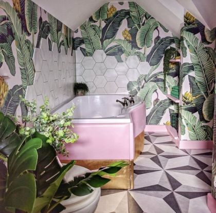 A-bright-tropical-bathroom-with-banan-leaf-wallpaper-marble-hex-tiles-a-pink-and-gold-clad-bathtub-is-lovely