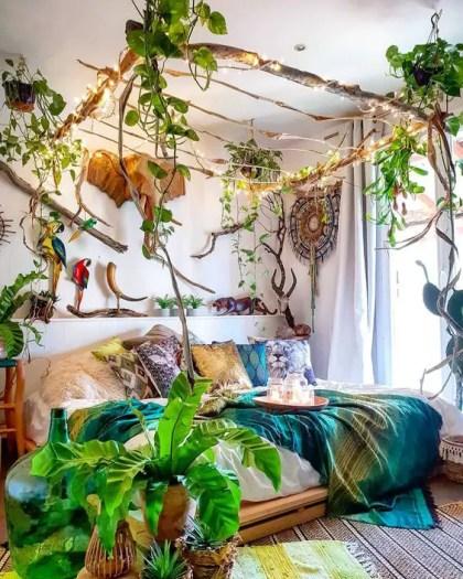 Ein-Dschungel-Themen-Schlafzimmer-mit-einem-Stock-Baldachin-mit-Lichtern-und-Kletterpflanzen-helle-Beet-Topfpflanzen-und-imitat-taxidermy