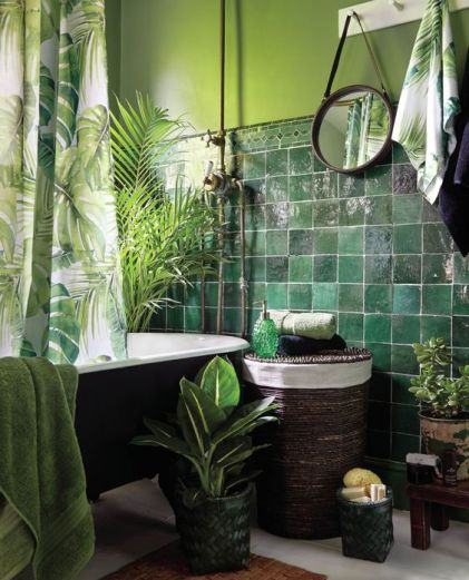 A-moody-tropical-bathroom-with-green-walls-and-dark-green-glossy-tiles-a-black-tub-a-woven-stool-potted-plants-and-tropical-print-textiles