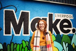 Woman outside standing against a painted wall that says 'Liverpool Make' in large letters
