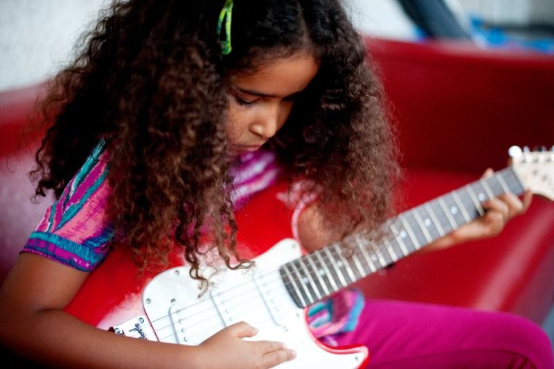 Black girl with long natural hair playing guitar black kids music article