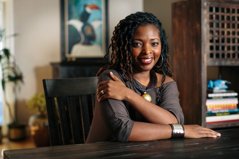 Denene Millner, smiling and sitting in a chair