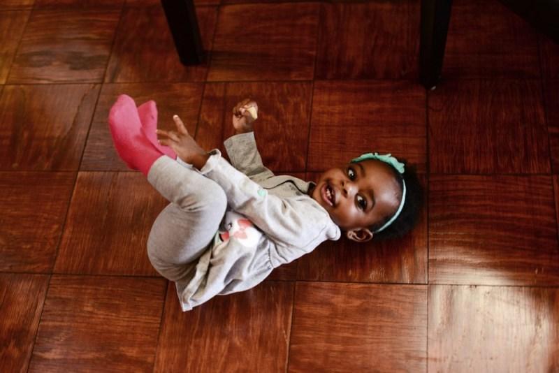 Black toddler rolling around on wooden floor black kids music article