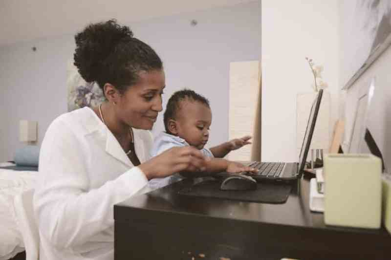Black mom working on laptop with son in lap