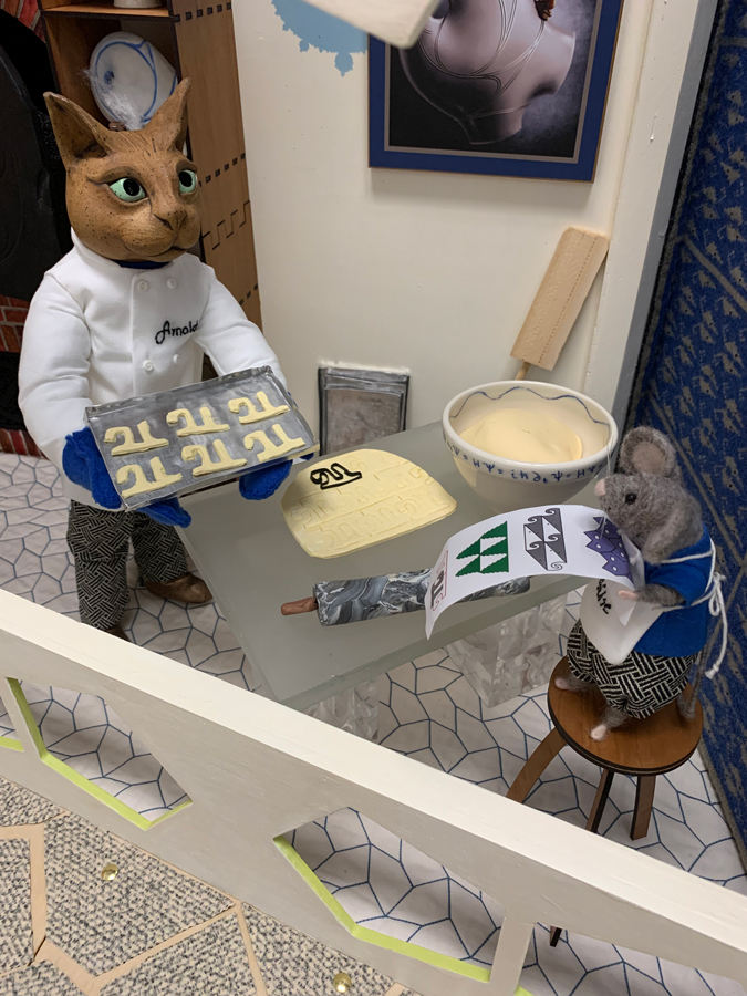 Arnold the cat making Pi-shaped cookies and his assistant