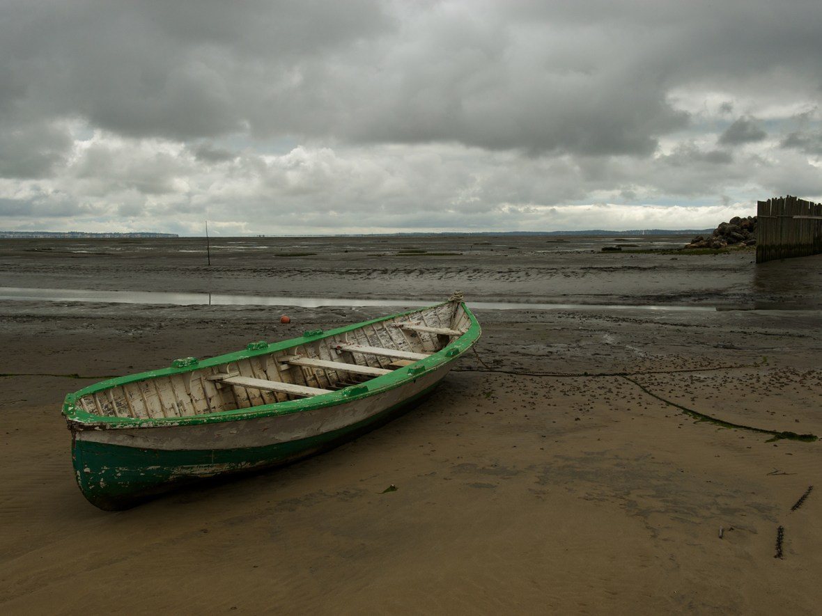 a wooden fishing boat stranded at low tide in the Arcachon Bassin, near Bordeaux, France