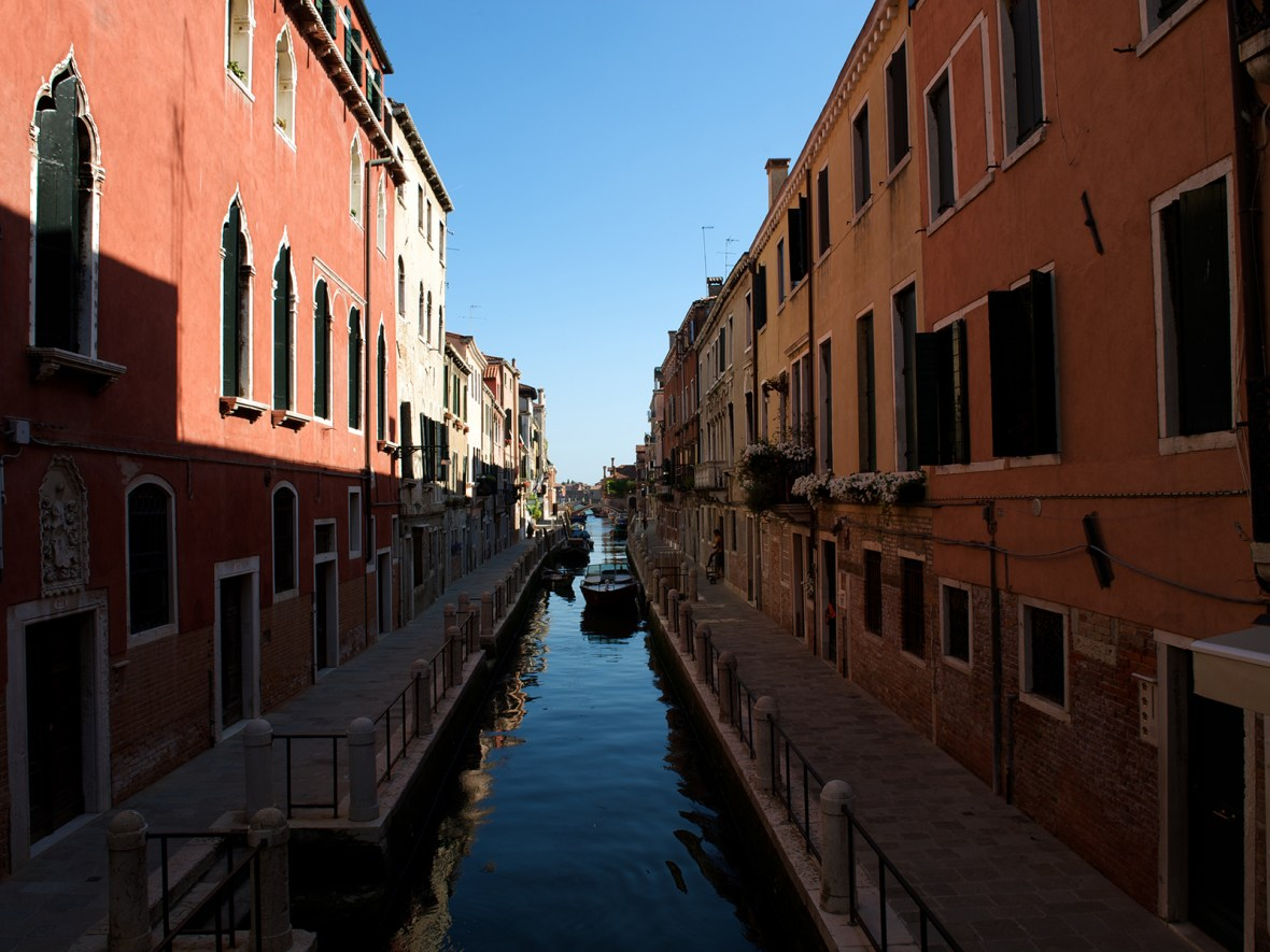 a canal surrounded by red buildings in the Dorsoduro neighbourhood of Venice, Italy