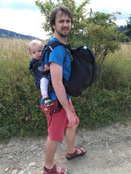 ojciec nosi dziecko w nosidle na plecach, z przodu ma plecak, wszystko podczas wycieczki górskiej