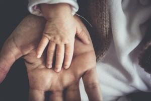 dorosły trzyma rękę dziecka