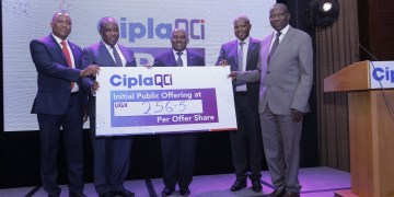 Hon. Matia Kasaija, Minister for Finance (Right) and Mr. Emmanuel Katongole, Executive Chairman Cipla Quality Chemical Industries Limited (middle) flanked by other officials unveil the CiplaQCIL Initial Public Offer Share price