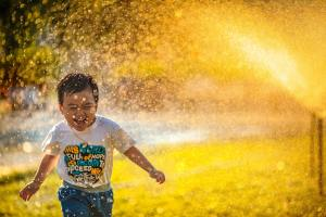 child running through sprinkler
