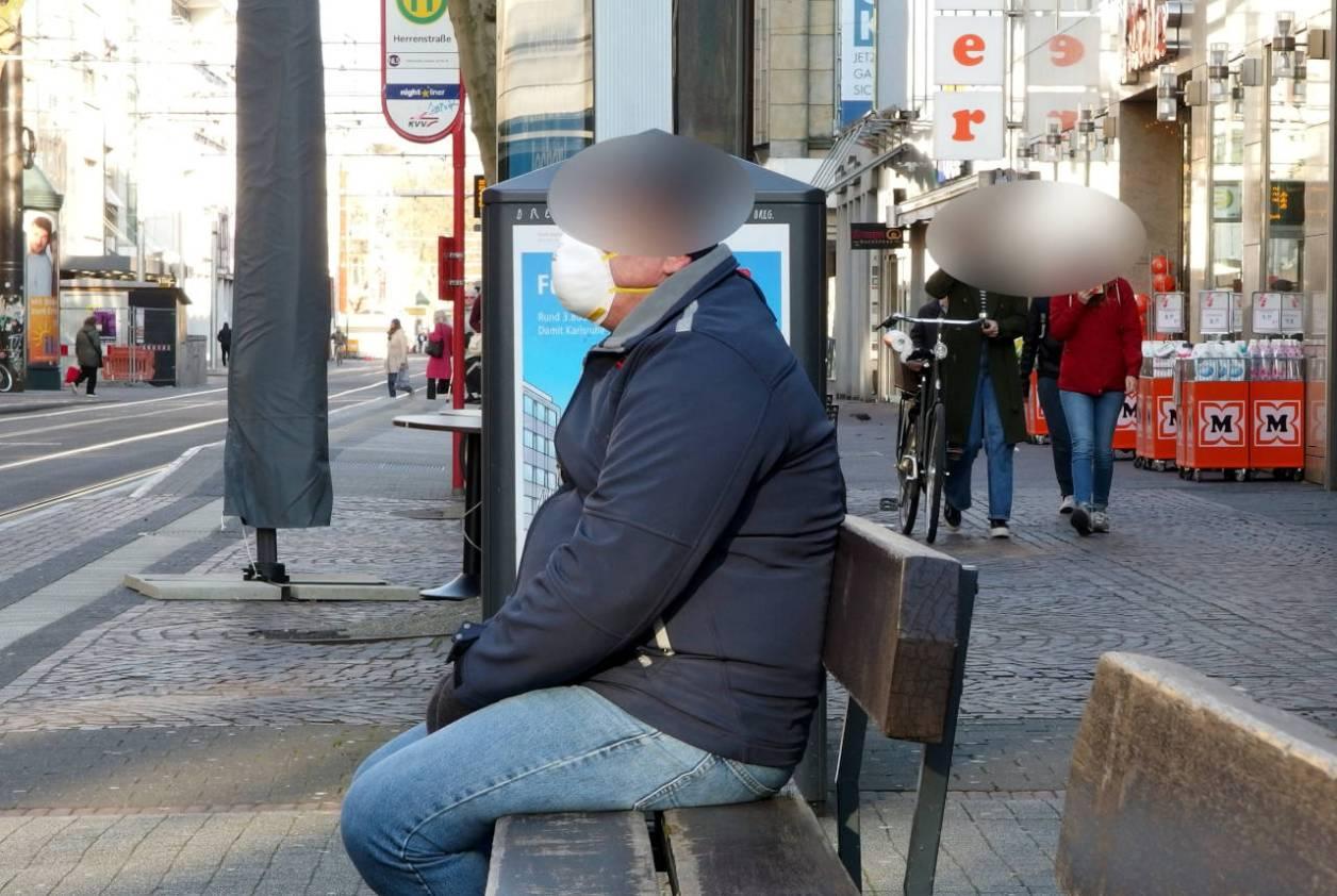 メインストリートのベンチに座る人。マスクを着用している © Matsuda Masahiro