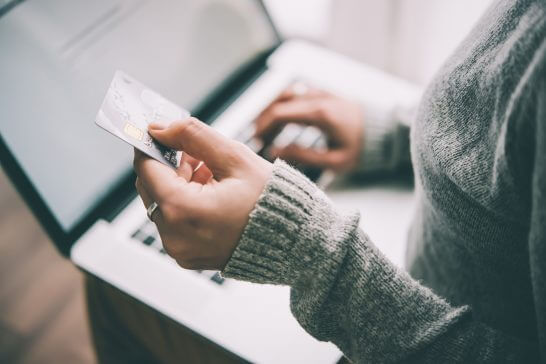 クレジットカードを見ながらパソコンを操作する女性