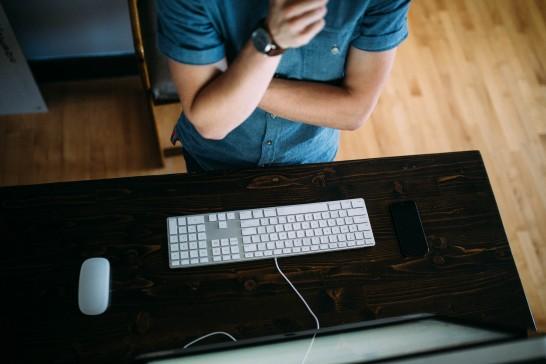 パソコンのモニターの前で熟考する男性