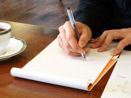 紙にペンで書いている様子