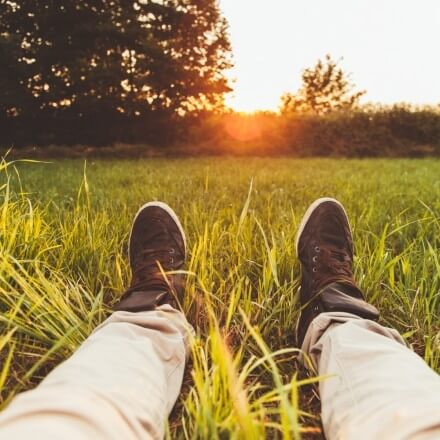 芝生に寝そべる人の靴