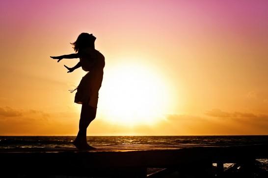 日差しの中、海外で手を広げる女性