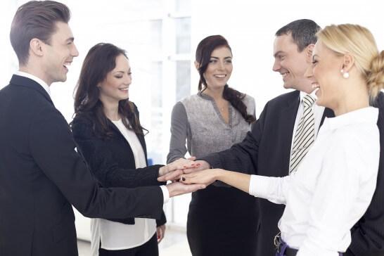 笑顔で手を合わせる外国人ビジネスパーソン