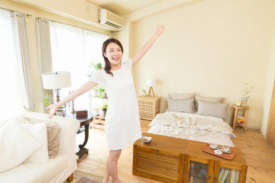 家の中で手を広げる笑顔の女性