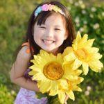ひまわりを持った笑顔の子供