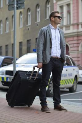 スーツケースを持ってあたりを見渡す外国人男性