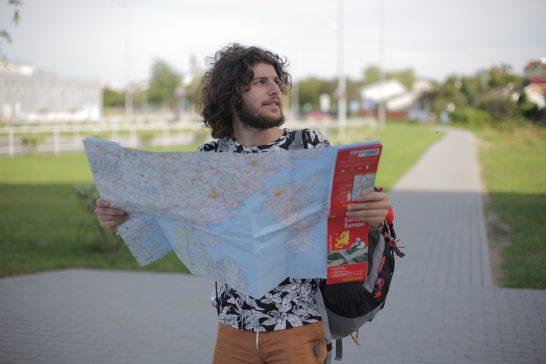 地図を広げて目的地を探す男性