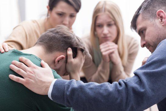 頭を抱える男性を見守る人々