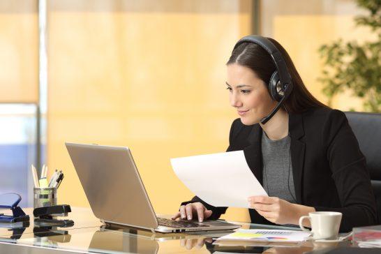 書類を持ちながらパソコンを見る女性