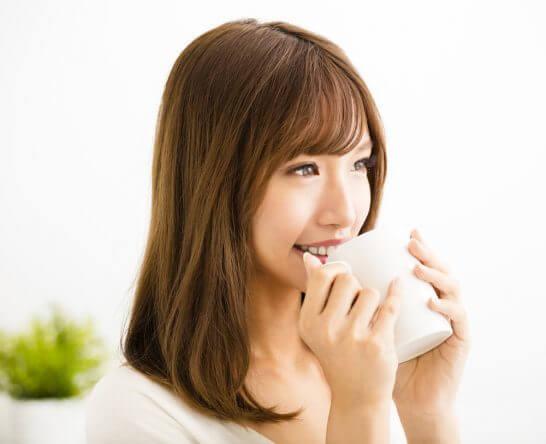 笑顔で飲みものを飲む女性