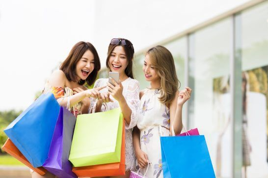 ショッピング中にスマホを見る女性