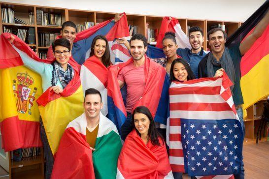 様々な国旗を身にまとう人々