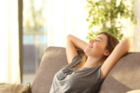 目を閉じてソファーでくつろぐ女性