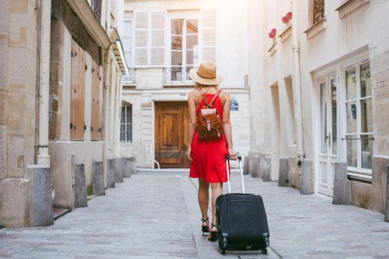 スーツケースを引きずる旅行中の女性