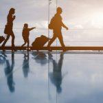 空港でスーツケースを運ぶ家族